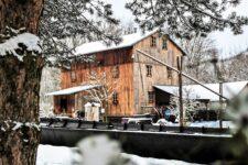 Zdjęcie przedstawia drewniany młyn. Na pierwszym planie barka rzeczna, a po prawej stronie drewniany żuraw przy studni. Pora roku - zima.