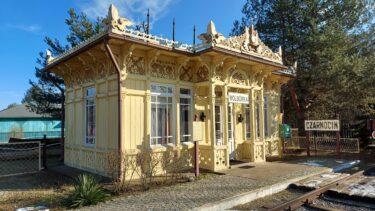 Drewniany zabytkowy budynek poczekalni kolejowej. Jest w kolorzez żółtym, ma bogate zdobienia ornamentowe. Świeci słońce, błękitne niebo.