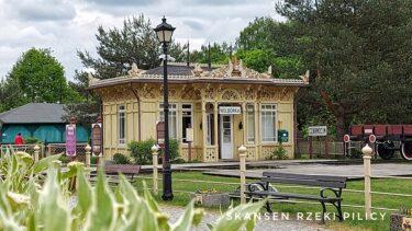 Zabytkowy drewniany budynek dawnej poczekalnu dworcowej, zwany stacyjką Reymonta. Elewacja w kolorze jasnożółtym. W tle drzewa pokryte zielonymi liśćmi. Przed budynkiem fragment torów kolejowych.