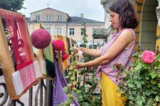 Młoda kobieta stojąca w ogródku. Przed nią na metalowym ogrodzeniu zawieszone są ramki tkackie i wełana w kłębkach. Kobieta coś tka.