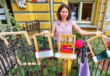 Młoda uśmiechnięta kobieta stoi przy ogrodzeniu w ogródku. Na płocie rozwieszone są ramki do tkania i kolorwa włóczka.