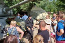 Grupa osób słucha opowieści mężczyzny ubranego w mundur czołgisty. W tle czołg i ciągnik opancerzony