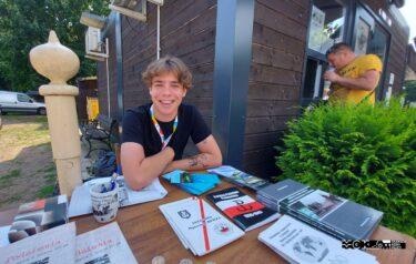 Młody chłopak siedzi przy stolku, na którym rozłożone sa książki i broszury o tematyce historycznej. Uśmiecha się.