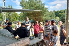 Grupa osób stoi przed czołgiem T-34