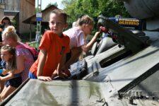 Dzieci napancerzu czołgu T-34. Jeden z chłopców patezy w obiektyw aparatu fotogtaficnego