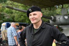 Mężczyzna w mundurze czołgisty. Lekko się uśmiecha. Ręce trzyma na biodrach.