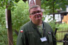 Mężczyzna w zielonym mudurze. Nosi okulary. Uśmiecha się.