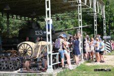 Grupa turystów oglądająca eksponaty militarne w skansenie.