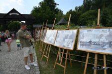 Mężczyzna ogląda wystawę złozoną z plansz ustawionych na sztalugach.