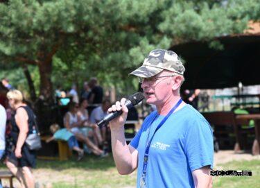 Mężczyzna w niebieskiej koszulce i czapce w panterkę daszkiem. W rece trzyma mikrofon, do którego mówi.