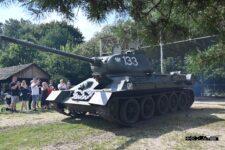 Grupa osób robi zdjęcia czołgowi T-34, który jest w trakcie jazdy.